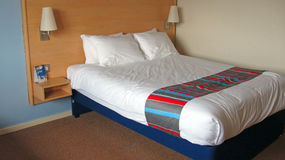 Chiuda su di un letto matrimoniale in una camera di albergo Immagini Stock Libere da Diritti