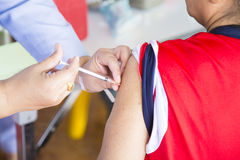 Chiuda su di un man& x27; il braccio ed il vaccino di s è iniettato dall'infermiere Fotografia Stock