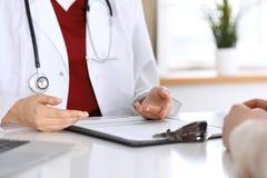 Chiuda su di un medico e delle mani del paziente mentre discutono le cartelle sanitarie dopo l'esame di salute immagine stock libera da diritti