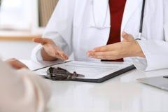 Chiuda su di un medico e delle mani del paziente mentre discutono le cartelle sanitarie dopo l'esame di salute immagini stock libere da diritti