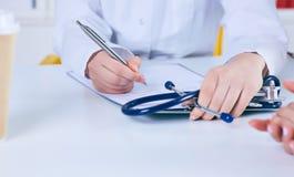 Chiuda su di un medico femminile che riempie un modulo di domanda mentre consultano il paziente Concetto di sanità e della medici immagini stock