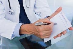 Chiuda su di un medico maschio che mostra uno strato in bianco di prescrizione Fotografia Stock