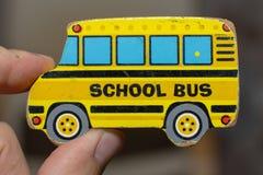 Chiuda su di un pezzo giallo di puzzle dello scuolabus del giocattolo consumato con una mano adulta Concettuale immagini stock