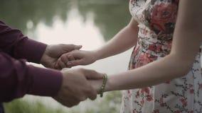 Chiuda su di un prender per manosi di due amanti La siluetta del dettaglio della tenuta della donna e dell'uomo consegna i preced stock footage