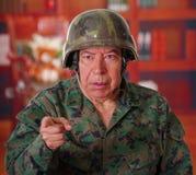 Chiuda su di un soldato di veterano serio che porta un casco e un'uniforme militare, indicando con il suo dito da qualche parte n Fotografia Stock