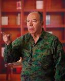 Chiuda su di un soldato di veterano serio che porta un'uniforme militare, indicando con il suo dito da qualche parte nell'vaga Immagine Stock
