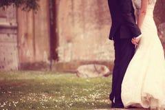 Chiuda su di un tenersi per mano dello sposo e della sposa Immagini Stock