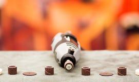 Chiuda su di un trapano con gli accessori della perforazione sulla tavola grigia in un fondo vago Fotografia Stock Libera da Diritti