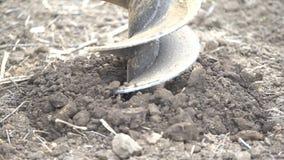 Chiuda su di un trapano funzionante, scavando un foro nella terra archivi video