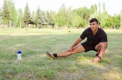 Chiuda su di un uomo che fa l'allungamento delle gambe sull'erba con l'orizzonte nei precedenti Immagini Stock Libere da Diritti