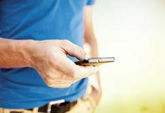 Chiuda su di un uomo che per mezzo del telefono cellulare Immagine Stock