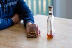 Chiuda su di un uomo che tiene un vetro di whiskey immagini stock