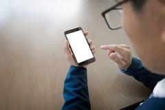 Chiuda su di un uomo d'affari facendo uso dello Smart Phone mobile sulla linguetta di legno immagine stock libera da diritti