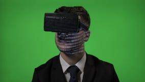 Chiuda su di un uomo del programmatore vestito nella codifica del vestito sui vetri della realtà aumentati vr sullo schermo verde archivi video