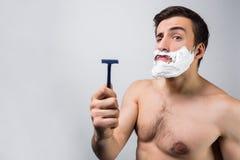 Chiuda su di un uomo topless che sta nella stanza bianca e che indica sul suo rasoio Pensa che questo sia il migliore rasoio abbi fotografia stock libera da diritti