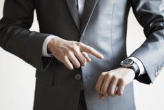 Chiuda su di un uomo in vestito grigio che indica all'orologio sul suo spirito della mano Fotografia Stock Libera da Diritti