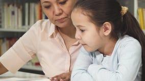 Chiuda su di una bambina sveglia che legge un libro con sua madre archivi video