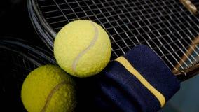 Chiuda su di una cinghia del tennis e di polso della racchetta della pallina da tennis nel nero con la riflessione qui sotto fotografia stock