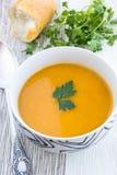 Chiuda su di una ciotola di minestra della carota, della zucca e della patata dolce Fotografia Stock