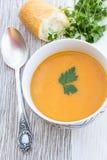 Chiuda su di una ciotola di minestra della carota, della zucca e della patata dolce Immagini Stock