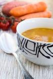 Chiuda su di una ciotola di minestra della carota, della zucca e della patata dolce Fotografie Stock Libere da Diritti