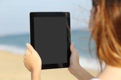 Chiuda su di una donna che mostra uno schermo in bianco della compressa sulla spiaggia Fotografia Stock