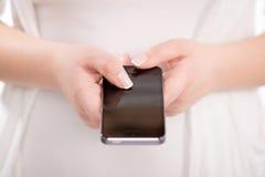 Chiuda su di una donna che per mezzo dello Smart Phone mobile Immagini Stock Libere da Diritti