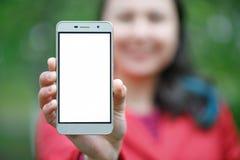 Chiuda su di una femmina che mostra uno schermo verticale in bianco del telefono sulla via immagini stock