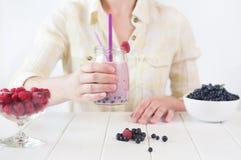 Chiuda su di una giovane donna che beve un frullato Fotografie Stock