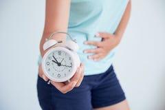 Chiuda su di una giovane donna malata con un orologio in sue mani il concetto del regolamento del ciclo mestruale tempo di prende Fotografie Stock Libere da Diritti