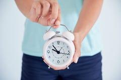 Chiuda su di una giovane donna malata con un orologio in sue mani il concetto del regolamento del ciclo mestruale tempo di prende Immagine Stock