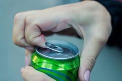 Chiuda in su di una mano che apre una bevanda fotografia stock libera da diritti