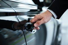 Chiuda su di una mano maschio che apre una porta di automobile Fotografie Stock Libere da Diritti