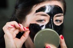 Chiuda su di una metà di decollo della giovane donna di bellezza di una maschera di protezione nera che esamina lo specchio Fotografie Stock Libere da Diritti