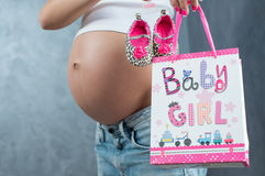 Chiuda su di una pancia incinta sveglia della pancia con il nastro rosa Immagine Stock
