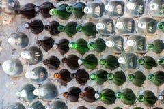 Chiuda su di una parete fatta delle bottiglie di vetro verdi e marroni immagine stock libera da diritti