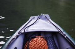 Chiuda su di una parte anteriore del crogiolo gonfiabile di canoa con il fiume o il lago Fotografia Stock