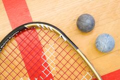 Chiuda su di una racchetta e di una palla di zucca sui precedenti di legno immagini stock