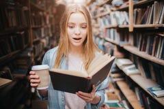 Chiuda su di una ragazza che legge un libro e che beve il caffè Il libro è così interessante lei può fermata del ` t che lo legge Fotografia Stock