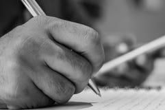Chiuda su di una scrittura della mano dell'uomo sul suo taccuino mentre tengono uno Smart Phone mobile Fotografie Stock Libere da Diritti