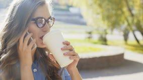 Chiuda su di una signora di affari che parlando sul telefono e sul caffè bevente video d archivio