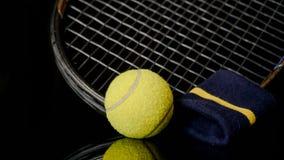 Chiuda su di una singola cinghia del tennis e di polso della racchetta della pallina da tennis nel nero con la riflessione qui so fotografia stock libera da diritti