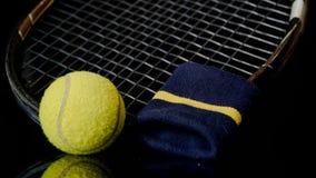 Chiuda su di una singola cinghia del tennis e di polso della racchetta della pallina da tennis nel nero con la riflessione qui so immagini stock