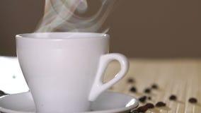 Chiuda su di una tazza bianca di caffè d'evaporazione sui semi di cacao torrefatti vicino della tavola archivi video