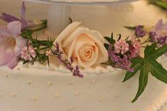 Chiuda su di una torta nunziale con i fiori Fotografia Stock