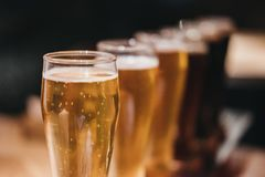 Chiuda su di uno scaffale dei generi differenti di birre, scuri per accendersi, su una tavola fotografia stock