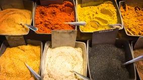 Chiuda su di vari generi di spezie variopinte e di curry in ciotole al mercato Immagine Stock