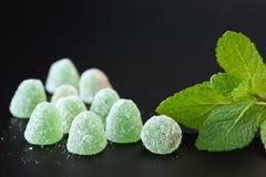 Chiuda su di verde, di gocce della gelatina di menta con i cristalli dello zucchero e delle foglie della menta verde su un fondo  fotografie stock libere da diritti
