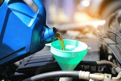 Chiuda su di versamento dell'olio fresco al motore di automobile nel servizio di riparazione automatica, olio del cambiamento fotografie stock libere da diritti