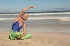 Chiuda su di yoga di pratica della donna senior mentre si siedono sulla sabbia Fotografia Stock Libera da Diritti